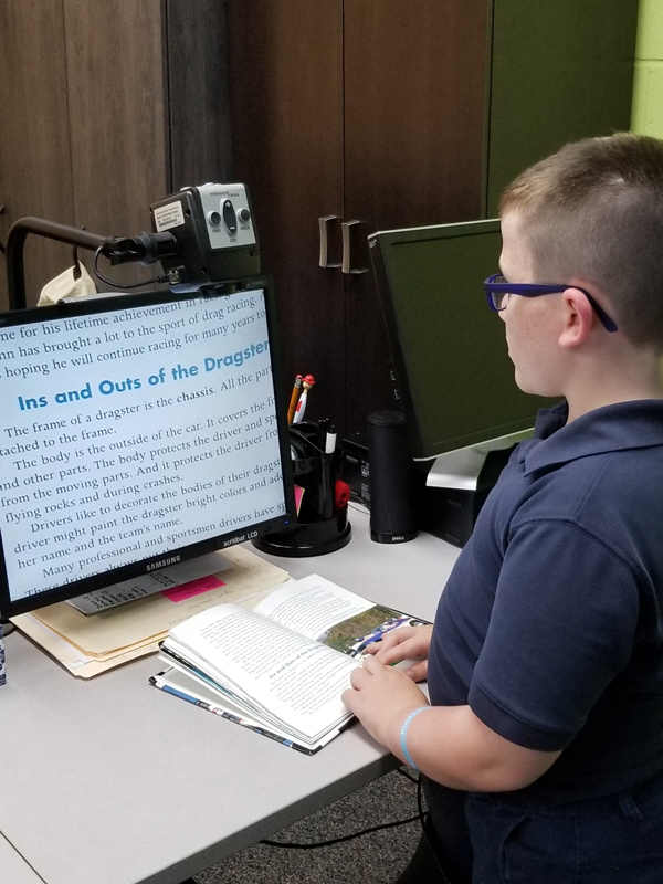 Lighthouse Kids student Randal using a screen magnifier to read