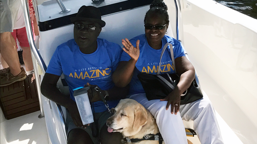 an image of two lighthouse clients and one of their guide dogs sitting in a boat smiling and waving