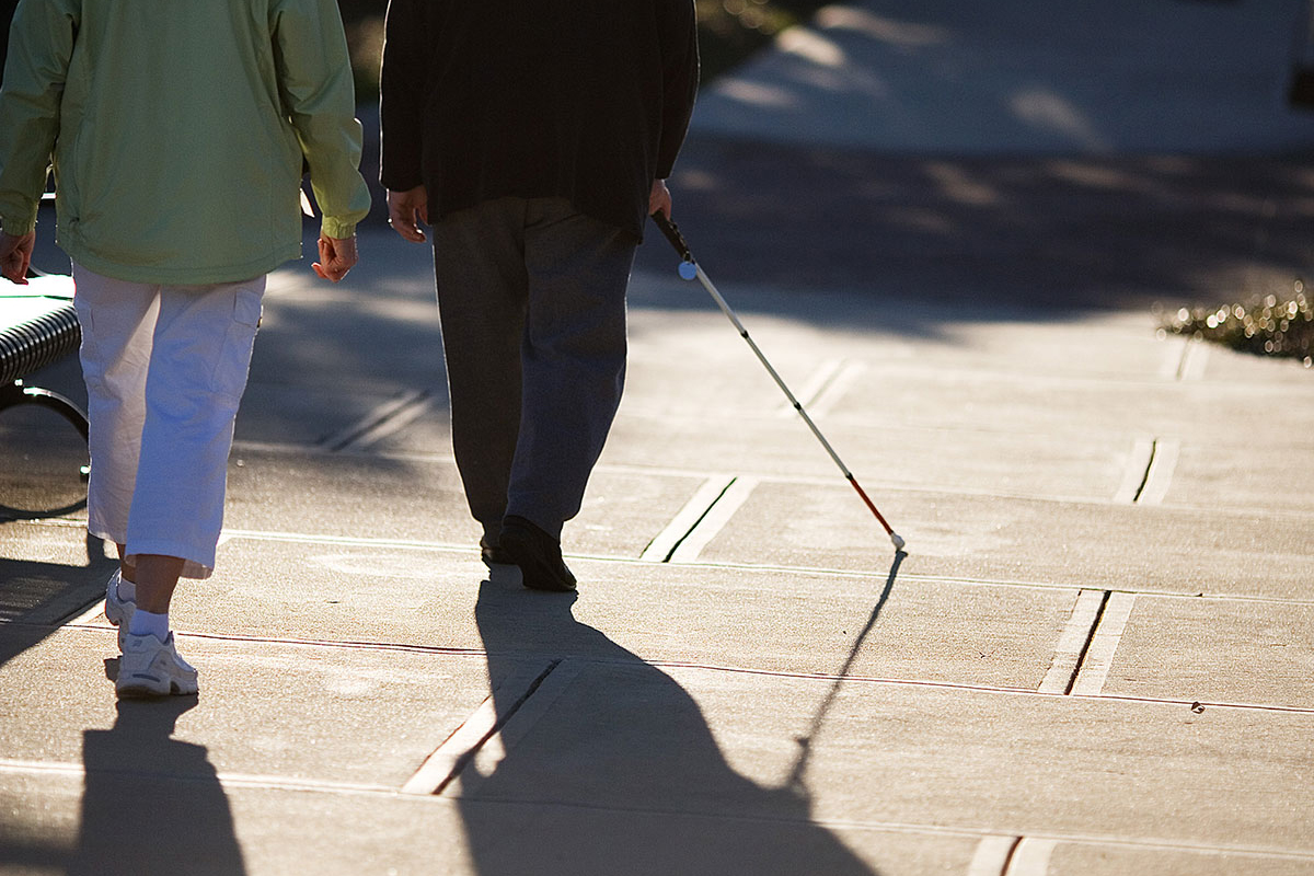 an image of an orientation and mobility instructor teaching a client on how to properly identify and use stairs outside of a building on a sunny day