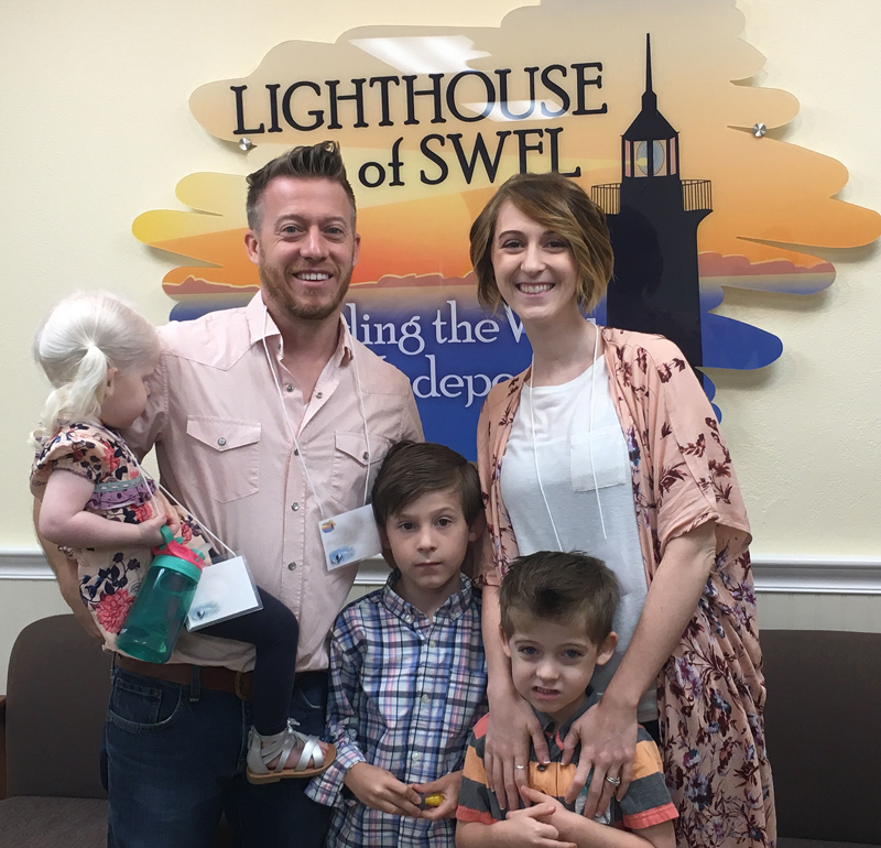 a picture of one of our families that have a child in the early intervention program, posing in front of the Lighthouse of Southwest Florida logo