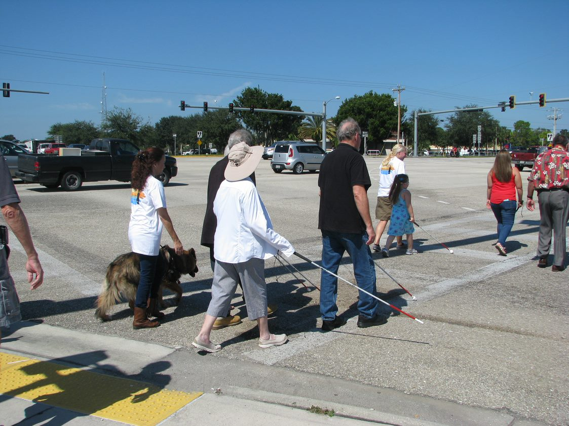 a group of people crossing the street under blindfold at a Lighthouse of Southwest Florida hosted White Cane day event